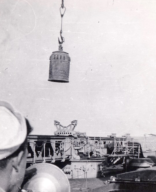 Salvaged Temple Bell being lowered into the fantail hangar deck CA-69 Boston