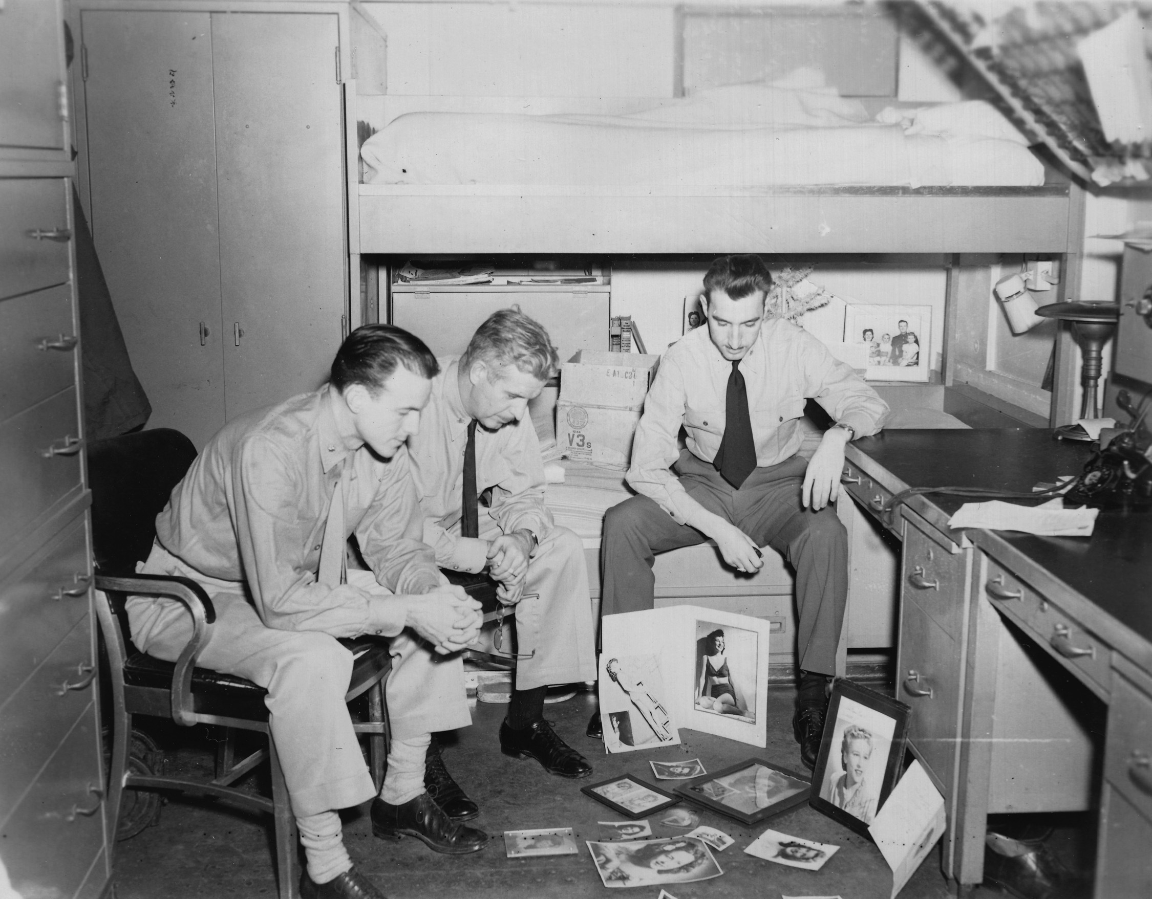 """Norm Bayley, (l) in his cabin on the Boston, judging """"prettiest girlfriend"""" contest, in Japanese Waters, Christmas 1945"""